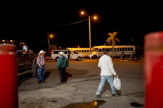 Busses wait to pick up farmworkers outside of La Fiesta #3 in Immokalee on Friday, April 3, 2020.