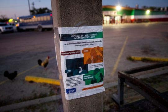 A sign showing the symptoms of COVID-19 hangs on a pole outside of La Fiesta #3 in Immokalee on Friday, April 3, 2020. Versions of the sign written in Spanish and Creole are posted around the area to spread information about the virus to members of the community that don't speak English.