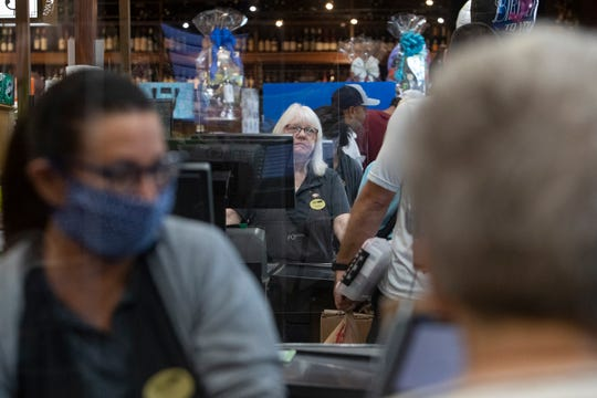 Wynn front end cashiers work behind a protective plexiglass shield, Friday, April 3, 2020, at Wynn's Market in Naples.
