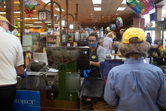 Frontend cashier Lisa Speiser works with customers, Friday, April 3, 2020, at Wynn's Market in Naples. Wynn's Market recently installed protective plexiglass shields to protect customers and employees from the coronavirus.