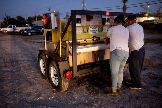 Norma Caldon, left, and Inocente Ordoñez, right, wash their hands before getting on a bus to work in Immokalee on Friday, April 3, 2020. The hand washing station, supplied by Lipman Family Farms, is one of many that have been placed throughout the community.