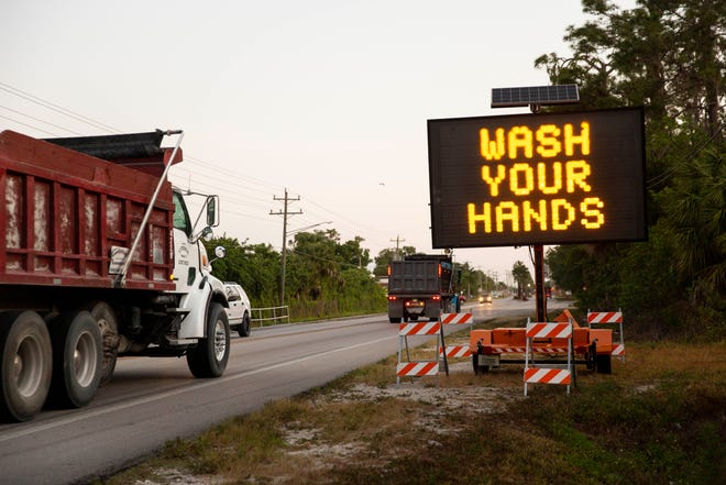 A sign along Immokalee Road encourages people to wash their hands and stay six feet apart to limit the spread of coronavirus in Immokalee on Friday, April 3, 2020.