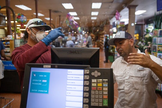Miguel Muniz, left, and Brian Galarza install a protective plexiglass shield to a register, Friday, April 3, 2020, at Wynn's Market in Naples.