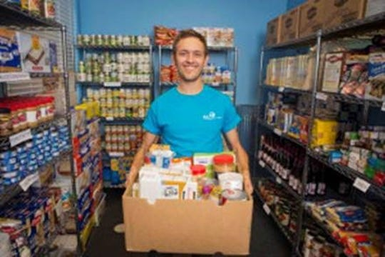 A volunteer keeps the Naples senior center food pantry shelves stocked with non-perishable food items and canned goods.