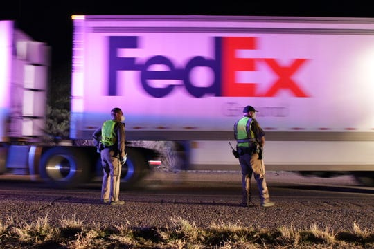 Navajo Police Officers Derek Drake, left, and Jose Oliva wait for a semi-trailer truck to pass the April 1 checkpoint on the westbound lane of U.S. Highway 64 in Hogback.