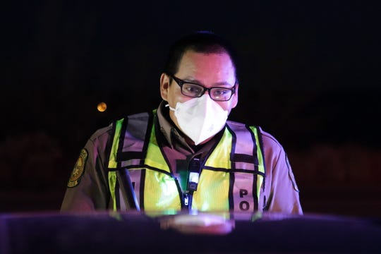 Navajo Police Officer Brandon Jim talks to a motorist about the curfew that restricts non-essential travel from 8 p.m. to 5 a.m. on the Navajo Nation.