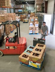 David Bohnke gets ready to load a pallet of food onto a truck at Feeding the Gulf Coast's warehouse in Milton on Friday.