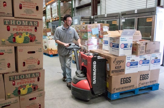 David Bohnke unloads food from a truck at Feeding the Gulf Coast's warehouse in Milton on Friday.