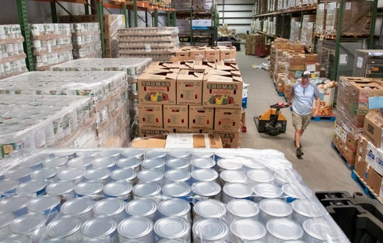 Steve Stager gets set to load food onto a truck at Feeding the Gulf Coast warehouse in Milton on Friday, April 3, 2020.