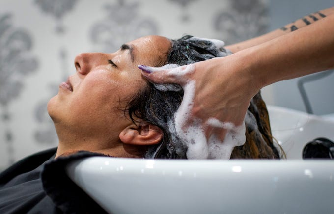 Dee Madden has her hair washed at The Savvy Stylist on a quiet Friday afternoon at the Tempe hair salon on April 3, 2020, just before Gov. Doug Ducey ordered hair and nail salons to be shut down by 5 p.m. on Saturday. Many people are avoiding hair care during the new coronavirus pandemic due to its hands-on nature.