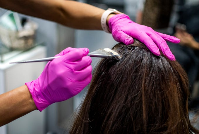 Heather Aguilar, owner of The Savvy Stylist, colors a client's hair at her salon in Tempe on April 3, 2020, just before Gov. Doug Ducey ordered hair and nail salons to be shut down by 5 p.m. on Saturday. Many people are avoiding hair care during the new coronavirus pandemic due to its hands-on nature.