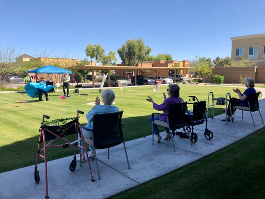 Residents at The Enclave at Chandler Senior Living made their way outside, some using walkers and wheelchairs, spacing themselves at least 6 feet apart on the sidewalk, to watch a show by Short and Sweet Entertainment.