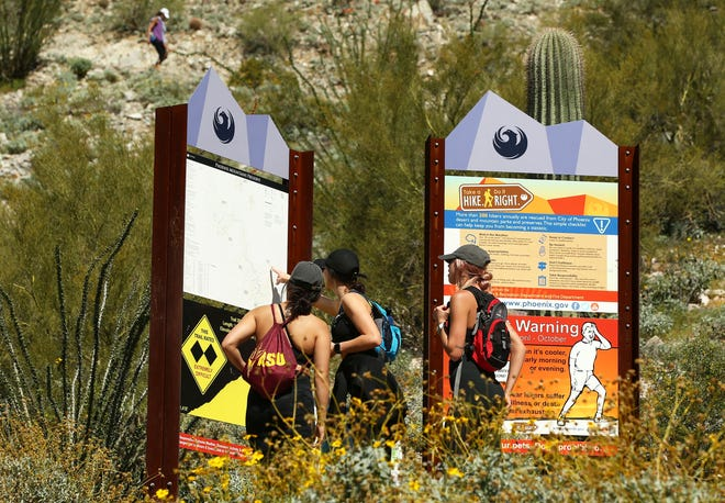 Hikers prepare to climb Piestewa Peak in the Phoenix Mountain Preserve on April 3, 2020, during the COVID-19 pandemic.