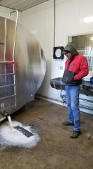 Perry County dairy farmer Donny Bartch watching his milk go down the drain. Bartch had to dump three days worth of milk this week.