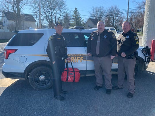 (from left): Marlette Police Chief Brian McGinnis and Sanilac County Sheriff Lt. Nathan Smith and Sgt. Matt Armstrong deliver meals for Sanilac County's meals on wheels program.