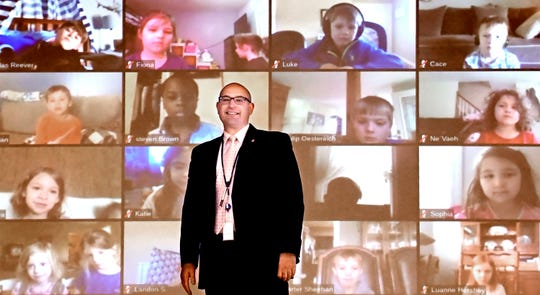 Todd Monos, Valley View Elementary principal, poses with a projected video feed showing the school's students watching a virtual concert by Steven Courtney, a Lancaster musician, Friday, April 3, 2020. Students watched the concert via the video conferencing platform Zoom. Monos hosted media at a showing of the concert at the school. Bill Kalina photo