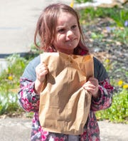 Naomie Hansen, 5, holds onto her lunch tight at Primo Pizza, April 2, 2020.