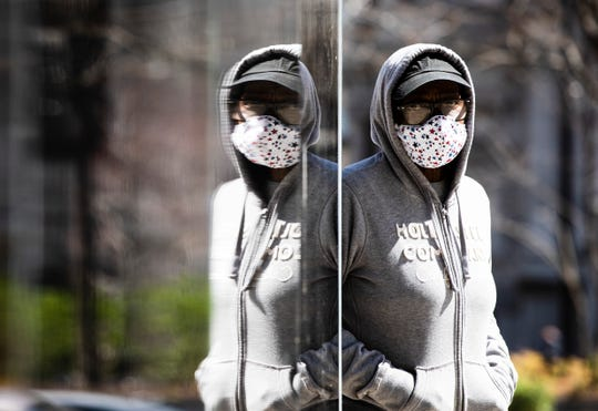 A person wearing a protective mask due to coronavirus concerns walks in Philadelphia, Thursday, April 2, 2020.
