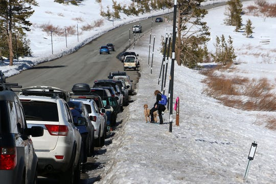 A woman prepares to take her dog snowshoeing at Tahoe Meadows near Reno on April 2, 2020.