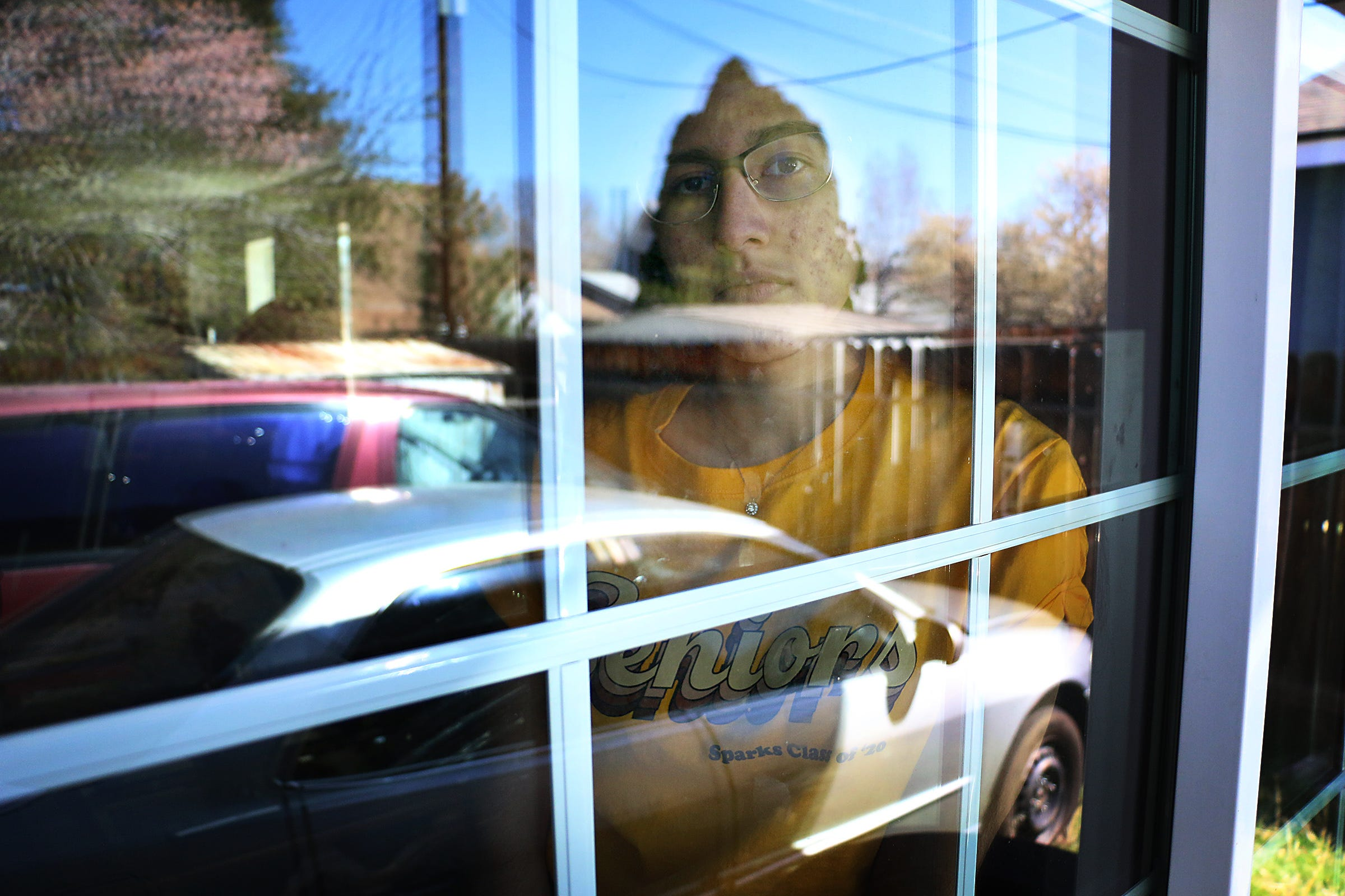Sparks High School senior Susy Meza poses for a portrait while looking through a window in her home on April 3, 2020.
