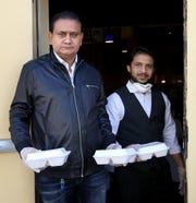 Owner Bishan Singh, left, and employee Anj Randive pose for a portrait while passing out free meals at India Kabab & Curry in Reno on April 3, 2020.
