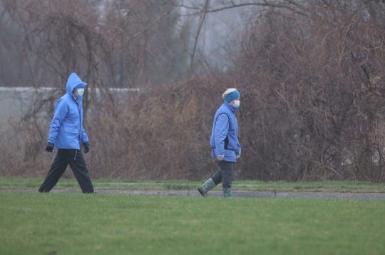 Some pedestrians wearing masks and gloves walk down Westfall Road in Brighton on Friday, April 3, 2020.