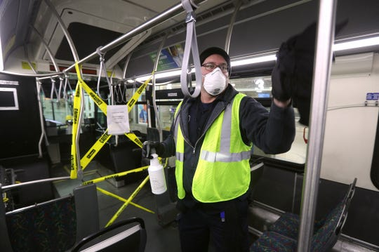Pablo Marte, with RTS, wipes down the interior of a bus at the transit center.  Every bus that comes though the transit center is wiped down before going back out its run.