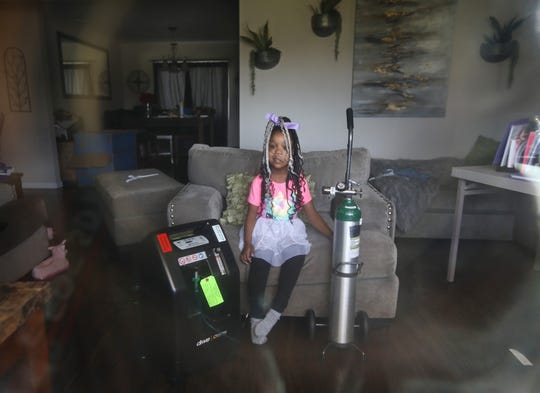 Brooke Ellis, 7, in the Ellis family's Brighton home. The family fears even visiting the grocery store — the coronavirus would endanger Brooke, who is medically fragile.