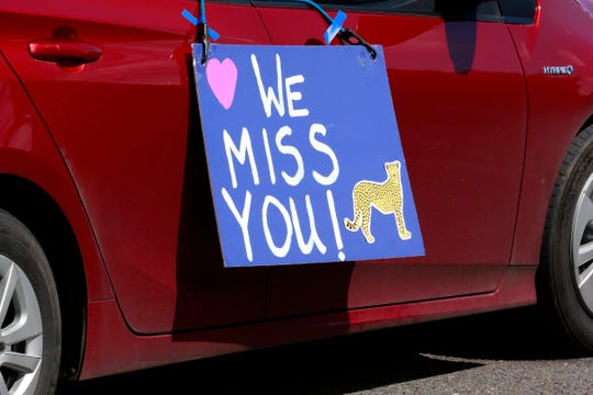 A homemade sign hangs from a car during a parade of Chapman Hill Elementary School teachers and staff in Salem, Oregon, on Friday, April 3, 2020.