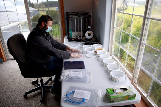 Kyle Kirsch assembles a face shield kit in his home near Silverton, Oregon, on Friday, April 3, 2020. He builds the kits out of plastic headbands that he prints from his four 3D printers and basic binding covers from an office supply store.