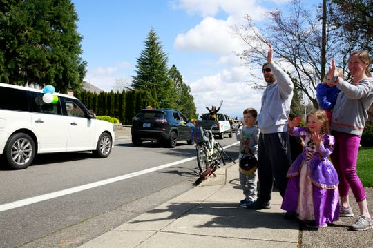 Andrew and Sarah Esterson and their kids Emmett, 6, (left) Lyza, 4, and Tessa, 2, wave as teachers and staff from Chapman Hill Elementary School drive past in a parade through neighborhoods in Salem, Oregon, on April 3, 2020. The event was organized as a way for the Chapman community to stay connected while practicing social distancing.