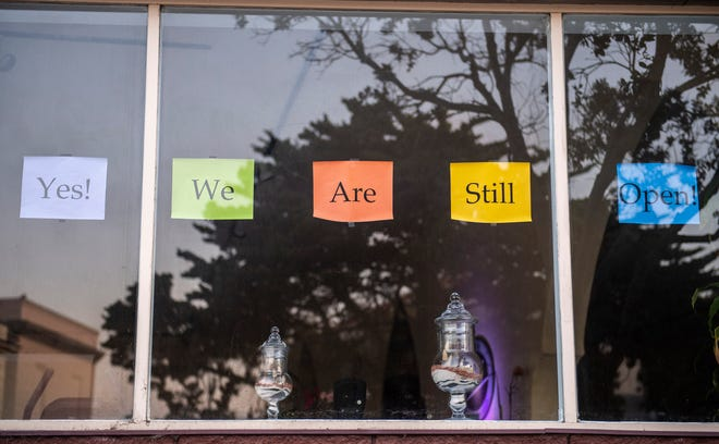 """A  sign that reads """"Yes we are still open,"""" is placed in front of a business in Pacific Grove."""