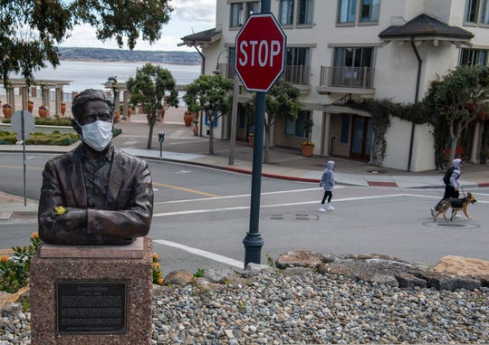A couple walks behind an Edward Ricketts statue with a face mask covering its face in Monterey.