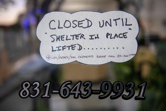 "A sign that reads ""closed until Shelter-in-place lifted"" is placed in front of a Pacific Grove business."
