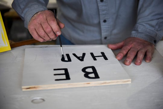 """Scott Huber paints """"Be Happy"""" on a sign on Thursday, April 2, 2020 in his garage in Sioux Falls, S.D."""