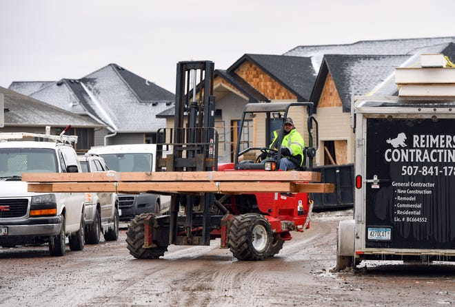 A construction worker drops off planks of wood at a home build site on Friday, April 3, on E. Piping Rock Avenue in Sioux Falls.