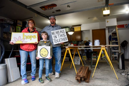 """Cyndy and Scott Huber make signs with encouraging words on them on Thursday, April 2, 2020 in their garage in Sioux Falls, S.D. The couple along with their grandson, Koi Retting, 8, decided to make """"Signs for the times"""" for people to take for free and display in their own yards."""