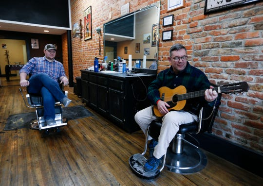Randy Steward plays the guitar at his son Chandler Steward's barbershop in Bolivar on Friday. Chandler said business has been down since the beginning of the pandemic, but he has seen clients traveling from Greene County to Bolivar because of the stay-at-home order closing barbershops there.