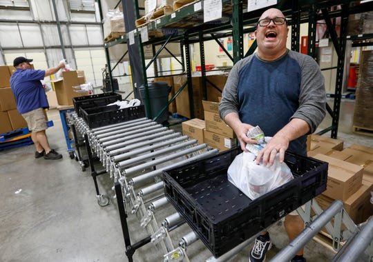 Carl Horton, right, a full-time substitute teacher, laughs as he helps assemble meals at Ozarks Food Harvest on Thursday. Horton is one of the 30 laid-off workers who have been hired by Ozarks Food Harvest.