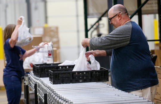 Carl Horton, right, a full-time substitute teacher, helps assemble meals at Ozarks Food Harvest on Thursday. Horton is one of the 30 laid-off workers who have been hired by Ozarks Food Harvest.