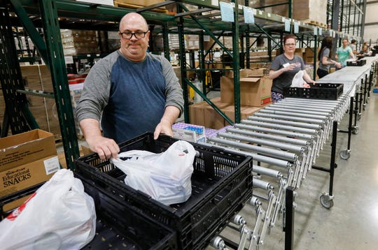 Carl Horton, left, a full-time substitute teacher, helps assemble meals at Ozarks Food Harvest on Thursday. Horton is one of the 30 laid-off workers who have been hired by Ozarks Food Harvest.