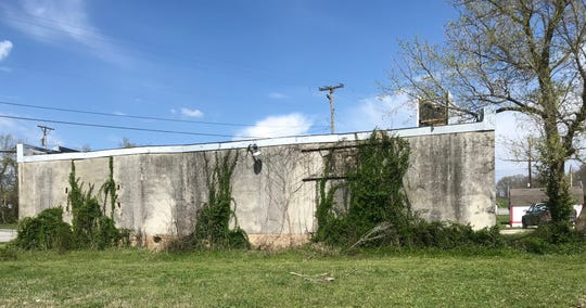 This small building has a concrete exterior that covers brick walls.  The side you see once had doors and it faces where the Chadwick Flyer railroad line once was.  A reader asked if it was once an ice house.