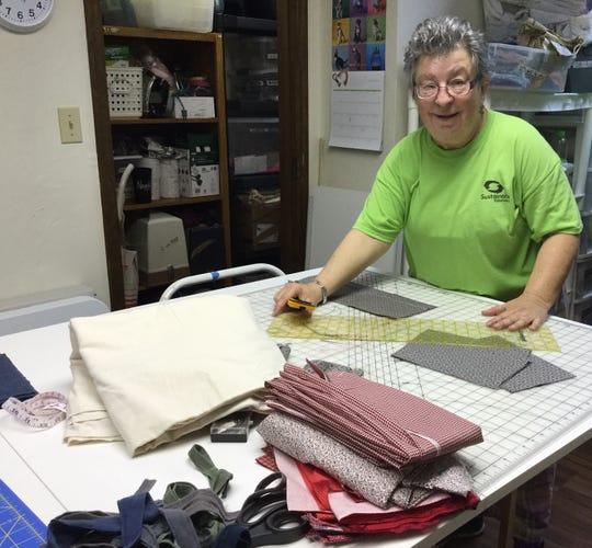 Volunteer Pam Doffek cutting the fabric for the masks.