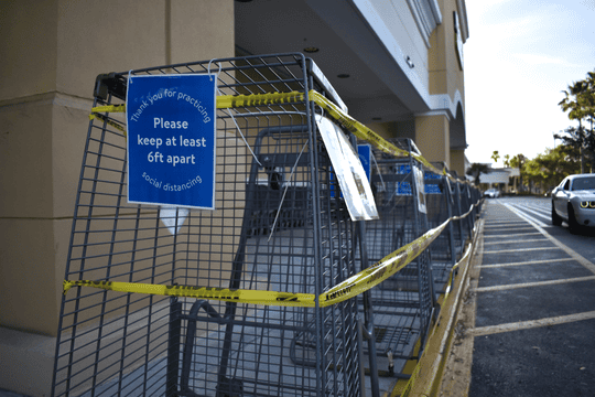 Caution tape and laminated signs encouraging social distancing adorn tipped shopping carts outside a Walmart Neighborhood Market in Port St. Lucie, Fla., Thursday, April 2, 2020. The store is open 7 a.m. to 8:30 p.m. daily during the coronavirus disease 2019 (COVID-19) pandemic.