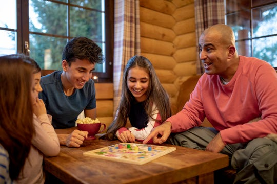 A family play a board game together in a log cabin.