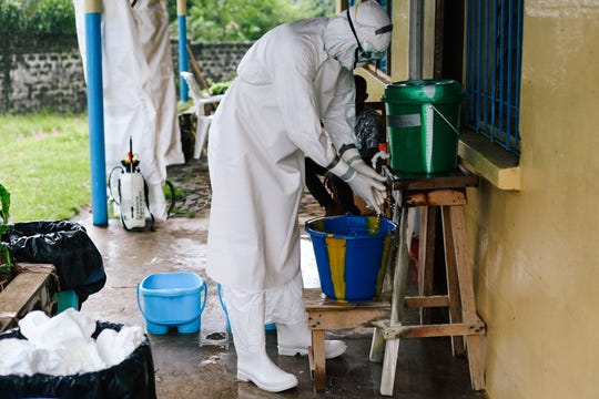 In this 2014 photo, Dr. John Fankhauser washes his hands with a special cleaner at ELWA Hospital in Liberia.