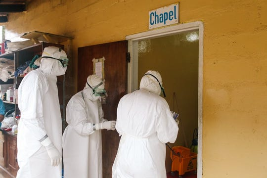 In this 2014 photo, Dr. John Fankhauser, far left, enters a chapel converted into an isolation unit for Ebola patients in Liberia.