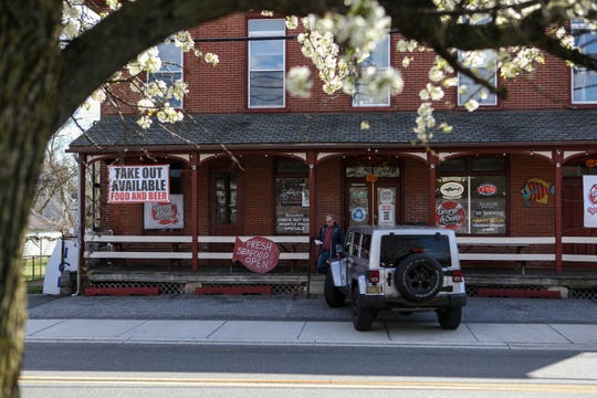 A sign outside George & Sons' Seafood Market and Oyster House announces that the store remains open for takeout food and beer, but the lot sits mostly empty amid the coronavirus pandemic on Thursday, April 2.