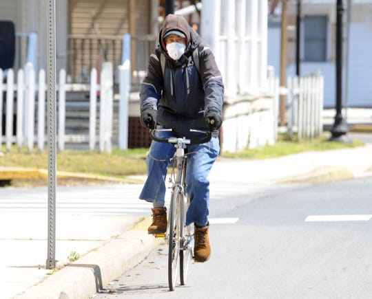 Edward Sample of Dover wears a protective mask as he pedals his bike west on Loockerman Street Thursday.