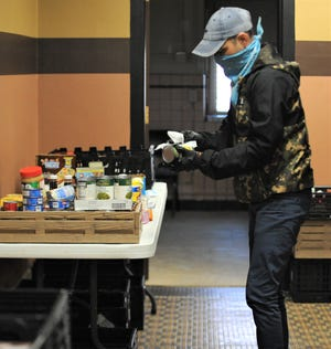 Volunteer Harley Dalton cleans and sorts canned food from the Hunger Network Food Drive at Secrest Auditorium. The collection of food and goods will be distributed to food pantries and three hot meal programs throughout Muskingum County. Additionally, former NBA player Kevin Martin gave Eastside Community Ministries $10,000 and the Muskingum County Community Foundation awarded the Hunger Network $25,000 from the Community Cares Fund.